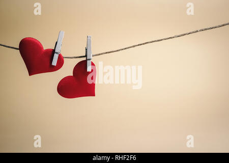 Couple of adorable red hearts hanging from a string by wooden pegs. Romantic Valentine's Day scene with copy space. - Stock Photo