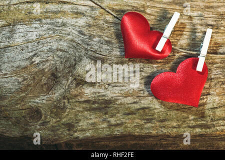 Two cute red hearts on string with clothes pegs on wooden background. Romantic Valentine's Day scene with copy space. - Stock Photo