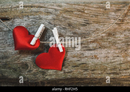 Couple of cute red hearts on string with pegs on wooden background. Romantic Valentine's Day scene with copy space. - Stock Photo