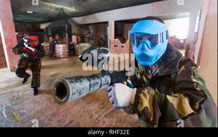 Portrait of blue team happy  positive player who is aiming in opponents on paintball field. - Stock Photo
