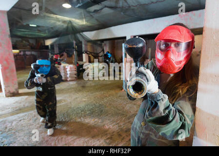 Portrait of red team happy positive player who is aiming in opponents on paintball field. - Stock Photo