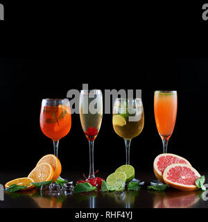 Composition with four different shapes crystal cocktail glasses with cold drinks, orange, lime and grapefruit slices, melting ice cubes, mint leaves and red cherries on black background. Ratio 1:1 - Stock Photo