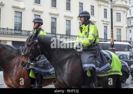 Two mounted policemen ride along The Strand through central London on horseback on a rainy day in February. - Stock Photo