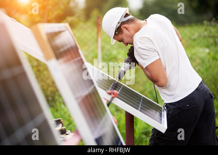 Profile of professional worker in helmet connecting solar photo voltaic panel to metal platform using electrical screwdriver outdoors on bright sunny day on blurred green rural landscape background. - Stock Photo