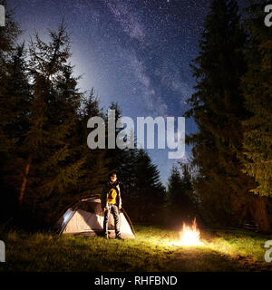 Camping site at night. Tourist tent on forest clearing and young hiker standing in front of burning campfire under dark blue starry sky on pine trees background. Beauty of nature and tourism concept. - Stock Photo