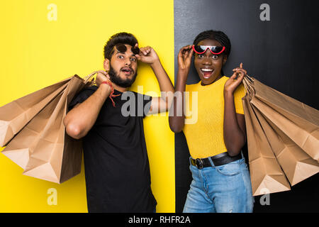 Young happy mixed race couple indian man and african woman in sunglasses shocked of sale with shopping bags standing on yellow black background - Stock Photo