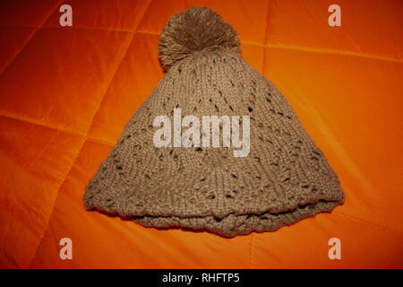brown knitted wool hat. the background is a bright orange winter duvet - Stock Photo