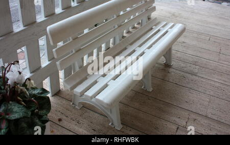 white plastic bench, old, on a paved sidewalk. a vase of flowers nearby. exterior decorations - Stock Photo