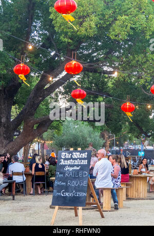 People sitting and eating and drinking under Chinesered lanterns at Fringe World Festival Russell Square Northbridge Perth WA Australia. - Stock Photo