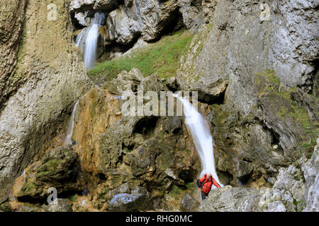 A climber pauses as he makes his way up the waterfall in Gordale Scar, Yorkshire Dales - Stock Photo