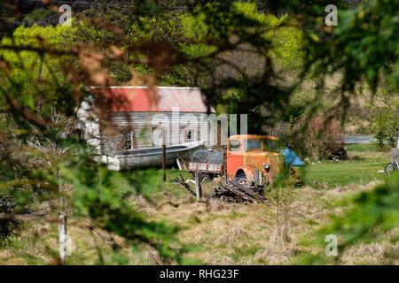 Vintage car next to farmhouse in South Island, New Zealand - Stock Photo