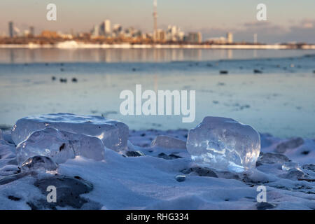 Panoramic Canadian winter landscape near Toronto, beautiful frozen Ontario lake at sunset. Scenery with winter trees, water and blue sky. - Stock Photo