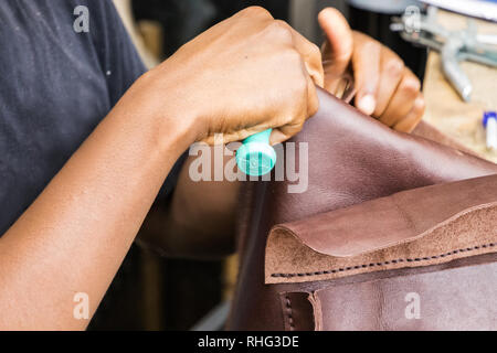 A male hand of a leather artisan sewing a leather bag at his workshop in the city center of Durban, South Africa. - Stock Photo