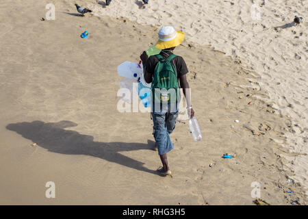 Durban, South Africa - January 7th, 2019: A south african black man collecting plastic bottles walking on the sand in a beach in Durban, South Africa. - Stock Photo