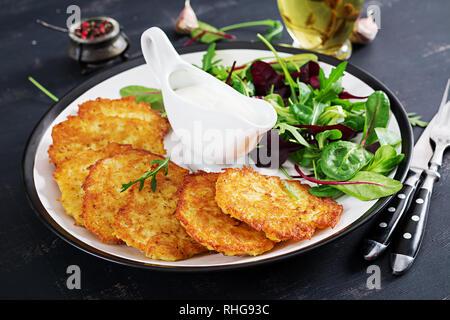 Potato fritters/draniki/pancakes served with sour cream. European cuisine. Kosher eating. Vegan food. - Stock Photo
