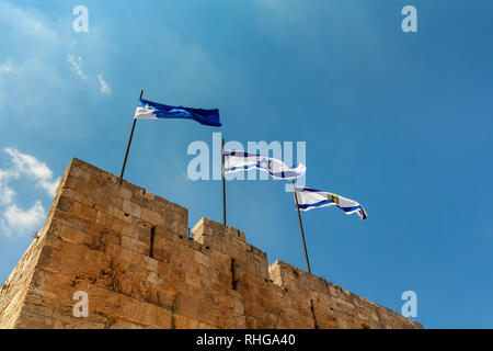 Flags of Israel and of Jerusalem waving on top of the Citadel walls wich surrounding Tower of David in Israel. - Stock Photo
