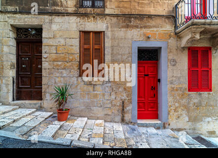 Front view of stone house with typical colorful wooden doors in Valletta, Malta. - Stock Photo