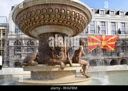 Skopje, Macedonia - May 2017: Lion and woman sculpture in city fountain with macedonian flag background. Skopje, Macedonia. - Stock Photo