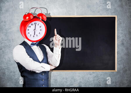 a man with a clock instead of a head on the background of a blackboard for chalk - Stock Photo
