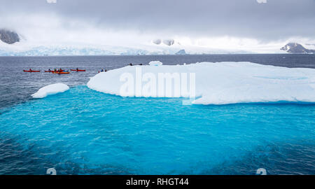 Huge iceberg with blue underwater part and small tourists kayaks with antarctic lagoon in the backgound, Peterman island, Antarctic peninsula - Stock Photo