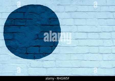 Drawn painted dark blue circle on light blue brick wall bricks surface of wall, as graffiti. Graphic grunge texture. Abstract background, stylish - Stock Photo