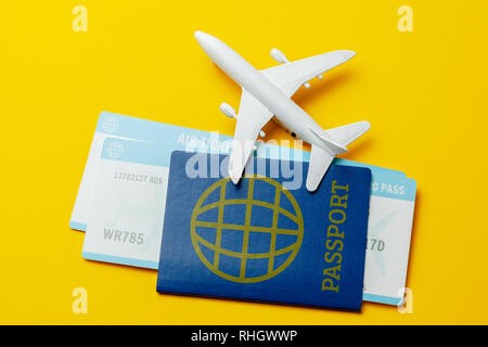 Tickets for plane and passport with model of passenger plane on yellow background. - Stock Photo