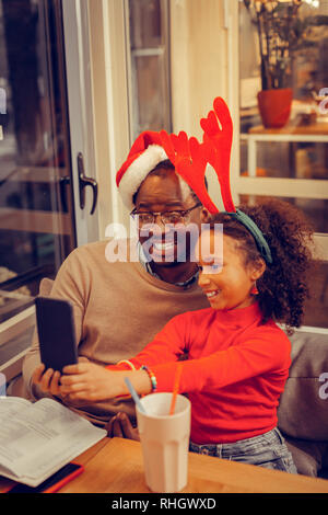 Cheerful father and daughter posing while making Christmas photo - Stock Photo