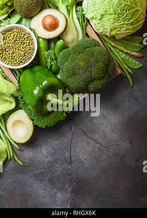 Assorted green toned raw organic vegetables on dark background. Avocado, cabbage, broccoli, cauliflower and cucumber with trimmed beans. - Stock Photo