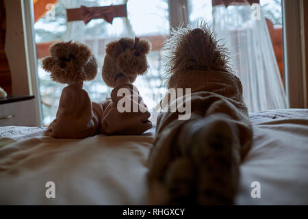 silhouette of brother and sister siblings looking outside window - Stock Photo