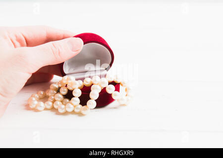Woman hand is opening jewellery box with pearls necklace with copy space, Valentine's Day or Womans Day gift concept - Stock Photo