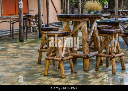 empty wooden furniture set, table with crutches, rainy day in the caring industry, garden and terrace furniture - Stock Photo