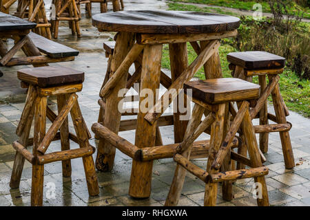 empty wooden table with bar crutches, garden or terrace furniture, rainy day in the catering industry - Stock Photo