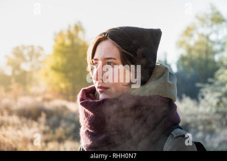 Backlit portrait of beautiful breath misting woman. Female person walking outdoors on chilly sunny morning in autumn