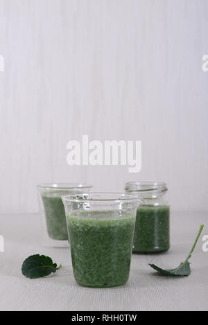 Three green smoothies supporting a raw, vegan lifestyle. Supports gut health and immune system. Made with Organic Ingredients. - Stock Photo