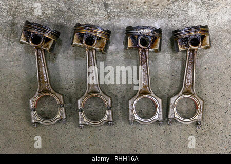 Four silvery metal car pistons in poor condition removed from the used engine in a deposit of oil lying on concrete in a vehicle repair shop for washi - Stock Photo