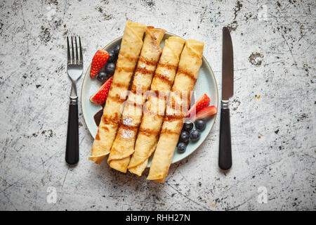 Plate of delicious crepes roll with fresh fruits and chocolate - Stock Photo