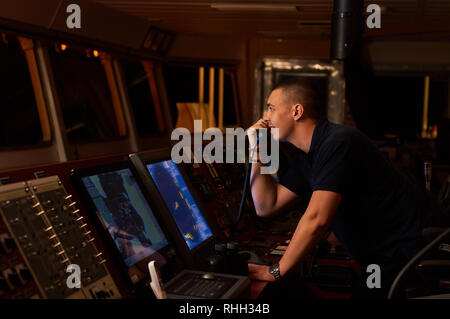 Navigation officer. Pilot on a bridge of a vessel underway with radio station and binocular in hands - Stock Photo