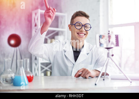 Beaming handsome student studying chemistry making video of his experiment - Stock Photo