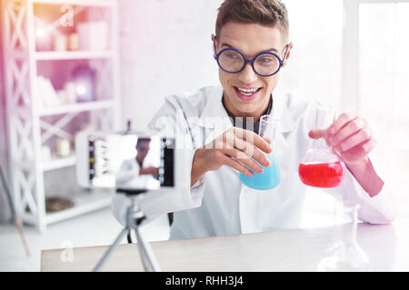 Student studying chemistry using photo stand making blog about experiment - Stock Photo