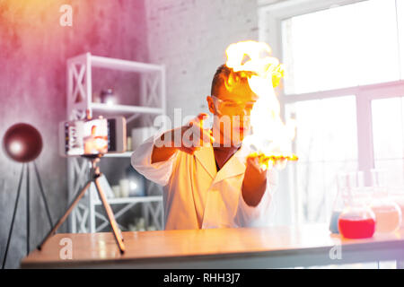 Handsome student wearing protection glasses making experiment with fire - Stock Photo