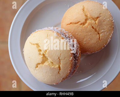 Top view of two Alfajores, traditional Latin American sweets served on a white plate - Stock Photo