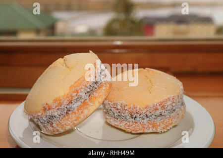 A Pair of Alfajores, Traditional Latin American Filling Cookies Served on Window Side Wooden Table, Ushuaia, Argentina - Stock Photo