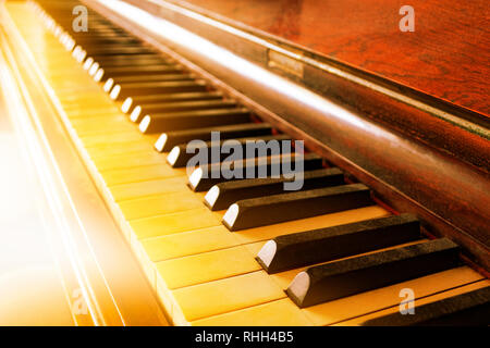 Closeup of antique piano keys and wood grain with sepia tone - Stock Photo