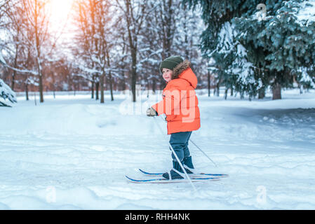Little boy 3-5 years old, happy standing on a skis. In a warm hat and jacket. The first steps in sports life. A strong, brave and confident child - Stock Photo