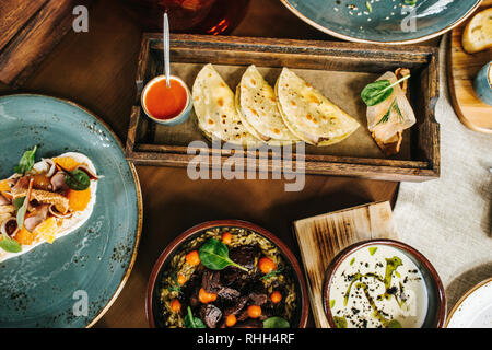 Variety of colorful cuisine served on wooden cutting boards and dishes. Cozy setting. - Stock Photo