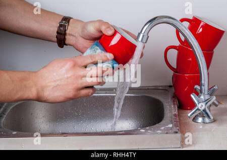 Male hands are washing red cups with sponge under running water in the kitchen sink - Stock Photo