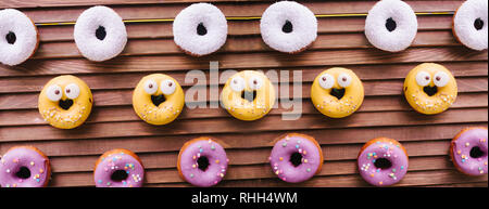 Yummy donuts hanging over wooden folding screen. White yellow and white coating. Glaze. - Stock Photo