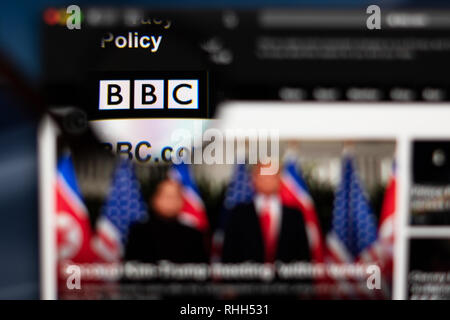 BBC News website homepage. BBC logo visible  through a magnifying glass. - Stock Photo