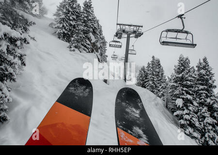 Ski chairlift bringing skiers and snowboarders up the mountain during heavy snowfall on a misty winter day in Courchevel, France. - Stock Photo