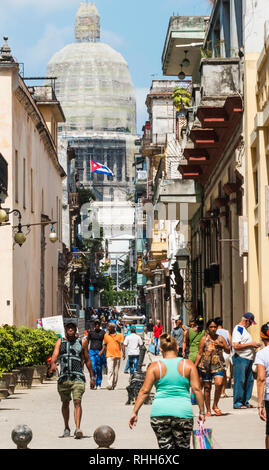 Havana, Cuba - 25 July 2018: People going about their day in Havana Cuba with Cuban flag and the Captiol building in the background. - Stock Photo